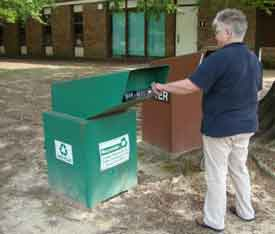 A visitor recycling a plastic bottle in a green recycling bin.