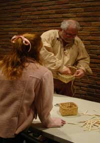 A visitor learns to make a basket with a demonstrator from the Tombigbee Pioneer Group.