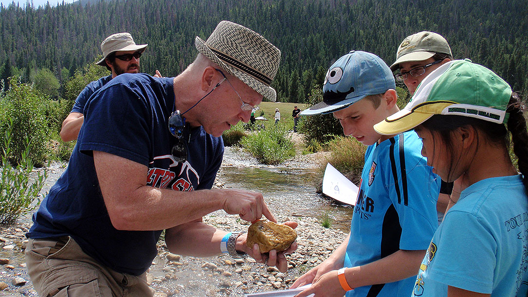 A professor points out dragonfly larvae to young BioBlitz participants