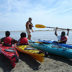 Three people sit in kayaks on the shore at Timucuan Ecological and Historic Preserve