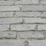 Close-up view of Belgian block pavers, which are rectangular, grayish and packed in with sand to pave streets in the historic district.