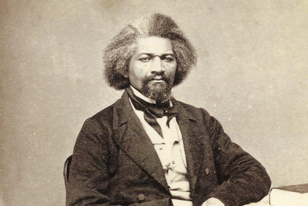Abolitionist Frederick Douglass sits at a table in 1863.