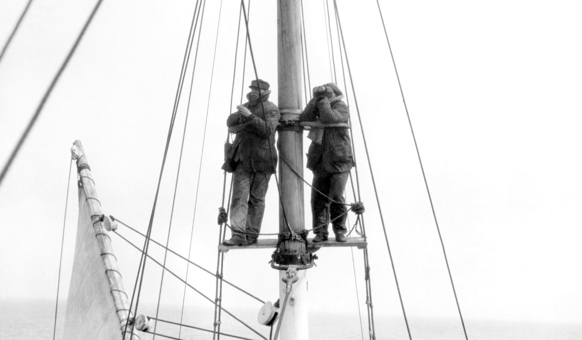 Two men stand at the crow's nest scanning for whales.