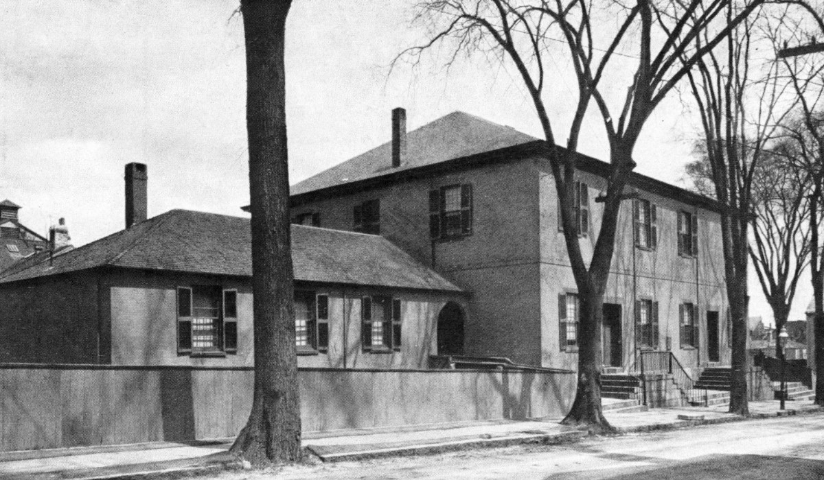 Black-and-white photo of meetinghouse, with two entrances, set behind trees.