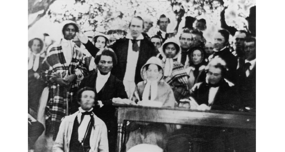 Black and white photo of Frederick Douglass leaning against a table among a crowd during an anti-slavery convention.