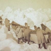 Men push a canoe over the snow and ice.