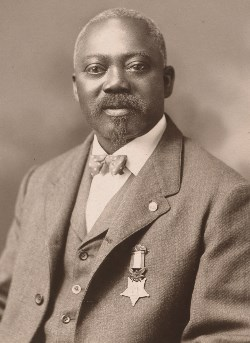 An older William Carney dressed in a suit with the medal pinned to his jacket.