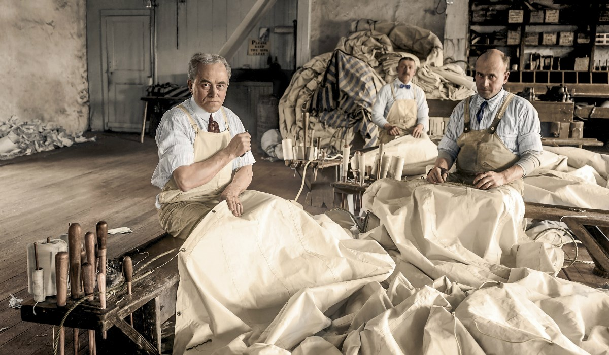 Colorized image of three men sewing sails during whaling error.