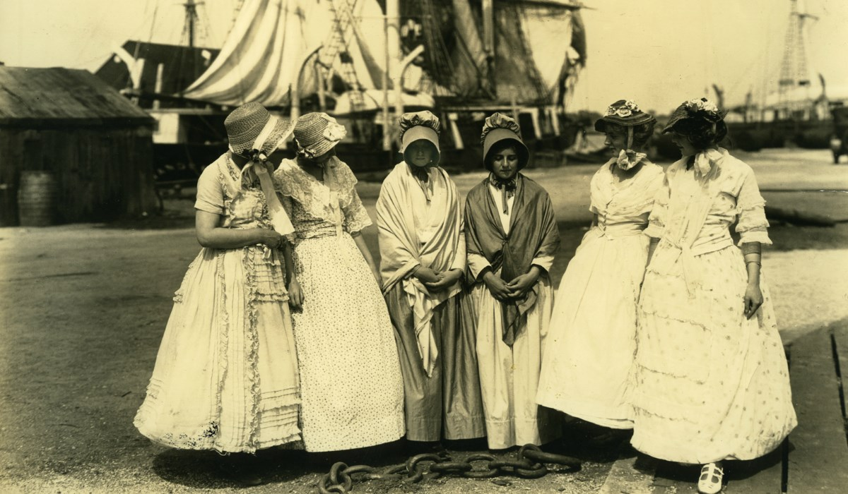 Sepia image of six women, gathered at docks in front of ships.