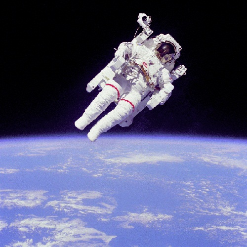 Astronaut floating in space with earth on the horizon.