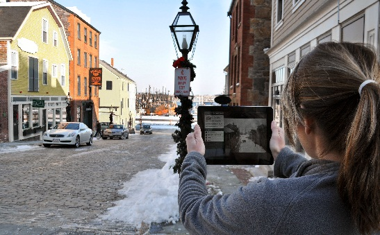 Girl holding an ipad looks at a historic image of the same street she is standing on now.