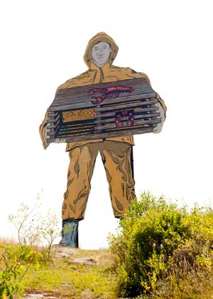 A display of a fisherman in a yellow slicker suit holding a lobster trap.