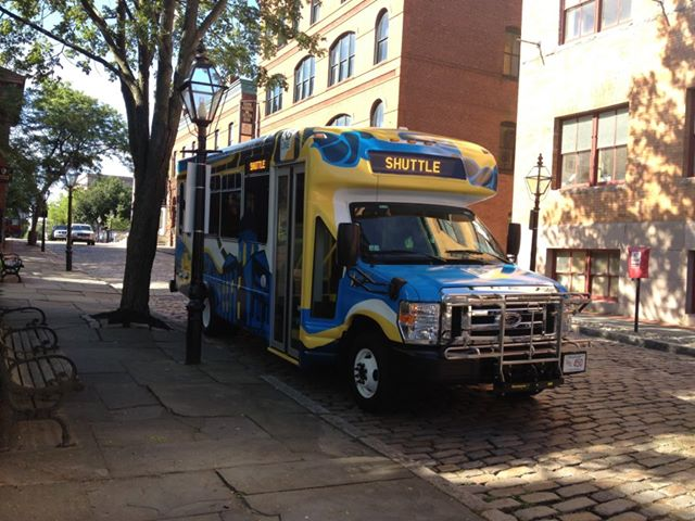 NB Line shuttle covered in blue and yellow graphics parked on second street.