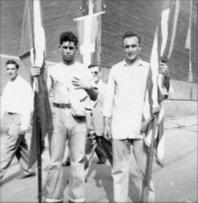 Black and white vintage photo of four men holding flags.