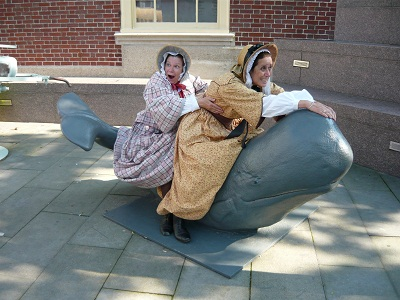 Ruth & Abby in 1850s dress on a whale sculpture smile in jest as the ride the whale.