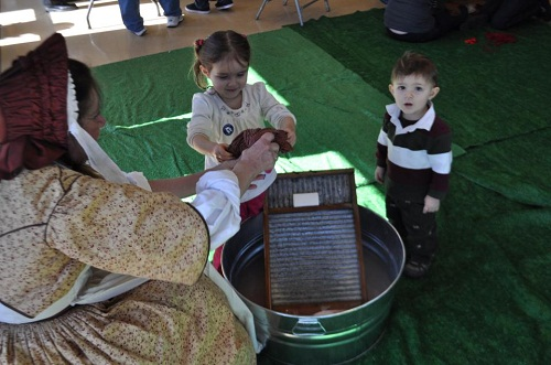 Ruth gets some help with the washing from two childen with her washboard, washtub and soap.