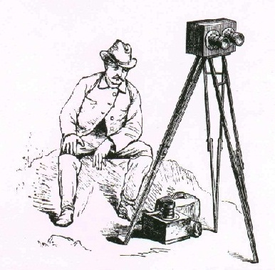 Mid-1800s man in period dress seated next to an early camera on a tripod.