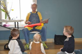Storyteller plays xylophone with three children watching and listening