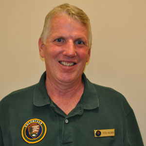 Photo of Peter Hacunda, NPS volunteer wearing dark green uniform shirt and volunteer patch.