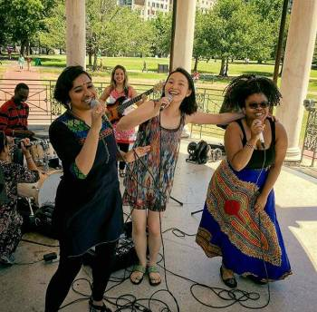 young men and women of various ethnic races and backgrounds playing music and singing joyously in an outdoor park setting