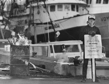 "young man holding an ""on strike"" placard stands next to a fishing boat at a dock"