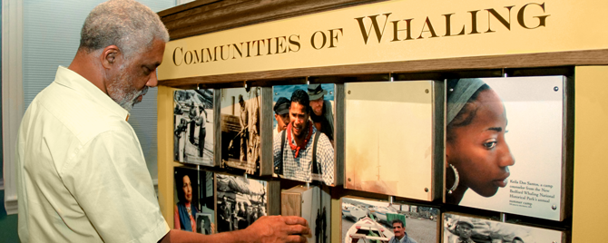 Visitor interacting with parks community of whaling exhibit.