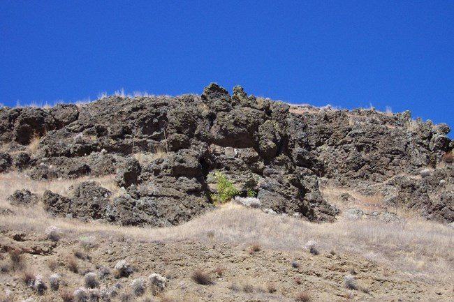 Dark colored basalt rock outcropping on hillside.