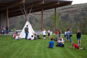 A ranger leading a program of school children around a tipi.