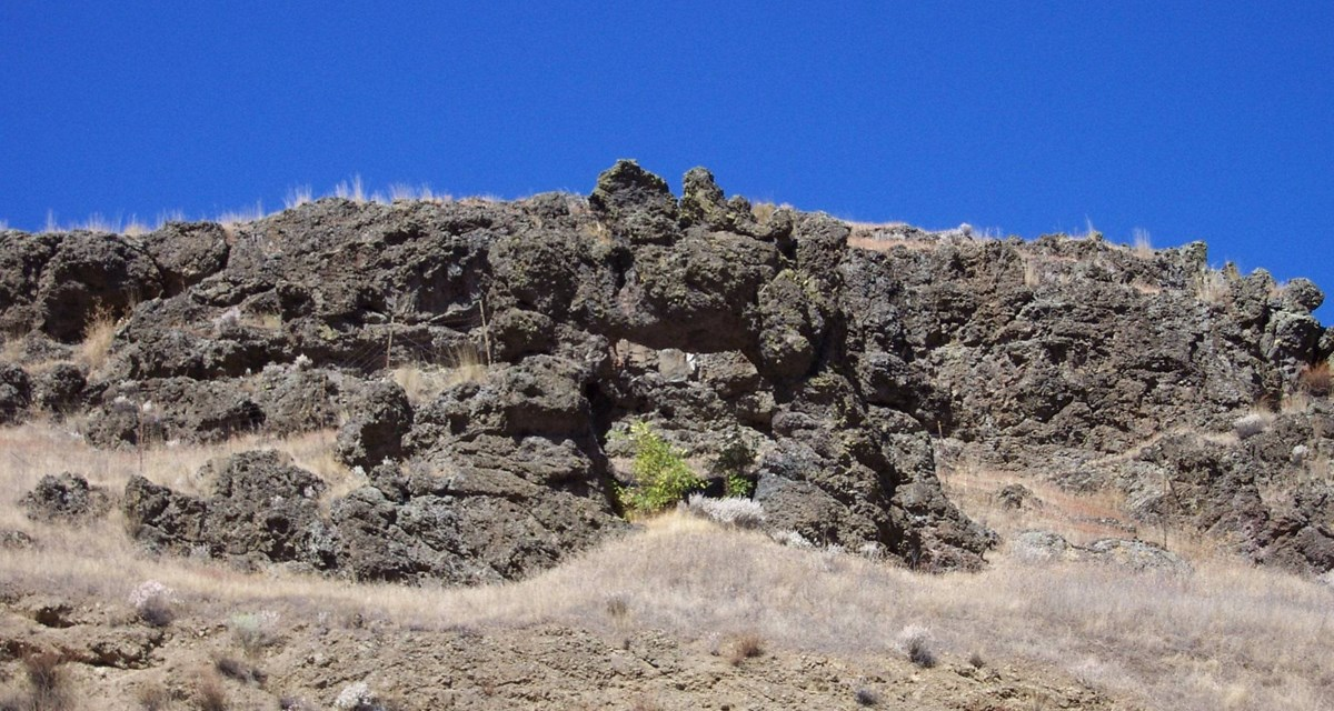 A basaltic rock outcropping on a hillside on a sunny day.