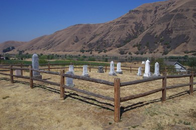 A fenced in cemetery with eleven headstones and the mountains in the background.