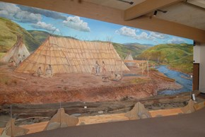 A museum display of a canoe with a mural of a Nez Perce fishing village with a large hut and tipis along a river as a backdrop.