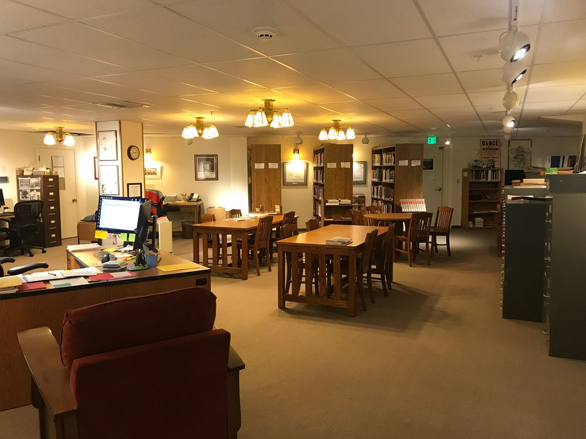 A room with many tables and chairs is empty. There are many file cabinets and bookshelves with books.