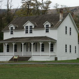 A white two story house with a porch and a wayside in front.