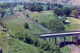 A view from above of railroad tracks going under a bridge.