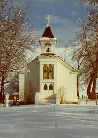 A white chapel during winter time with snow on the ground.