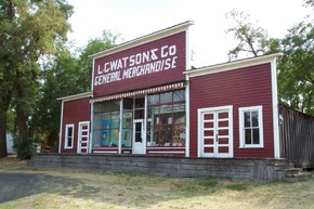 "A red and white store front with the sign ""L.C Watsons & Co General Merchandise."""