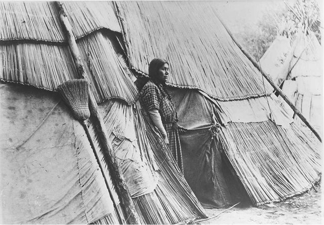 Woman stands in front of a tule lodge.