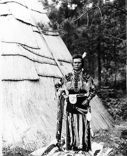 Man in front of tule mat structure dressed in traditional Nez Perce clothing.