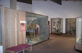A room with museum exhibits and display cases filled with traditional Nez Perce clothing, tools, weapons, and ceremonial objects.