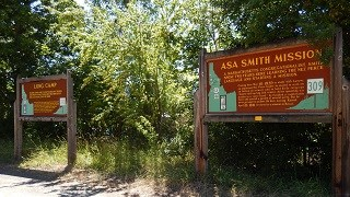 Two interpretive signs, one for Asa Smith Mission, and one for Long Camp stand on a highway pullout with trees in the background.