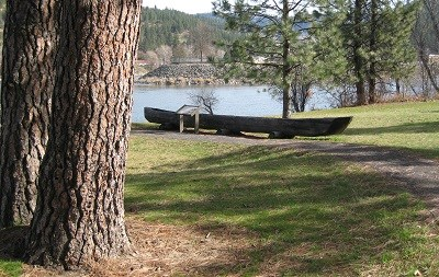 A wooden canoe sits in a grassy setting with a river in the background.