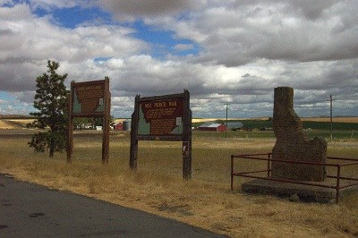 A highway pullout with two interpretive signs and a monument in the shape of Idaho on a cloudy day.