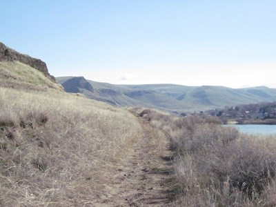 A hiking trail on a grassy hillside with a river in the background.