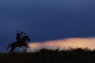 A metal silhouette of a Nez Perce warrior on horseback with the sunset in the background.