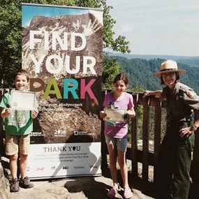 "Ranger and kids by ""Find Your Park"" sign"