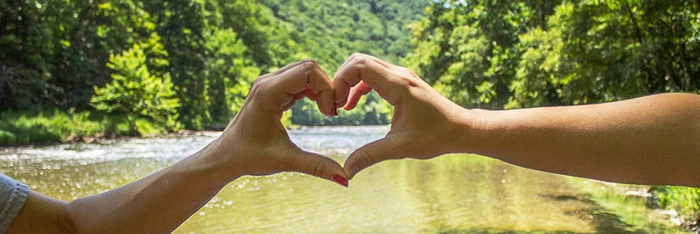 two hands form a heart over a river