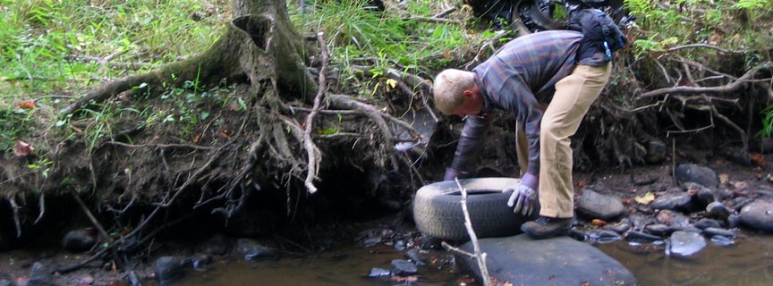 volunteer pulling a tire out of a stream