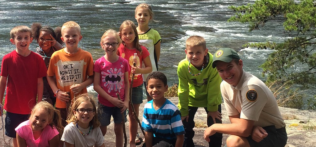 Kids and park volunteer along the river