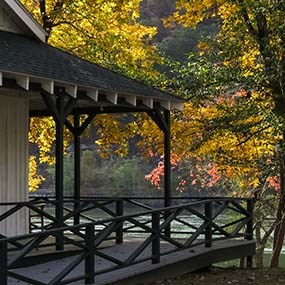cabin porch overlooking river with fall colors