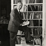 Carter G. Woodson standing by bookcase